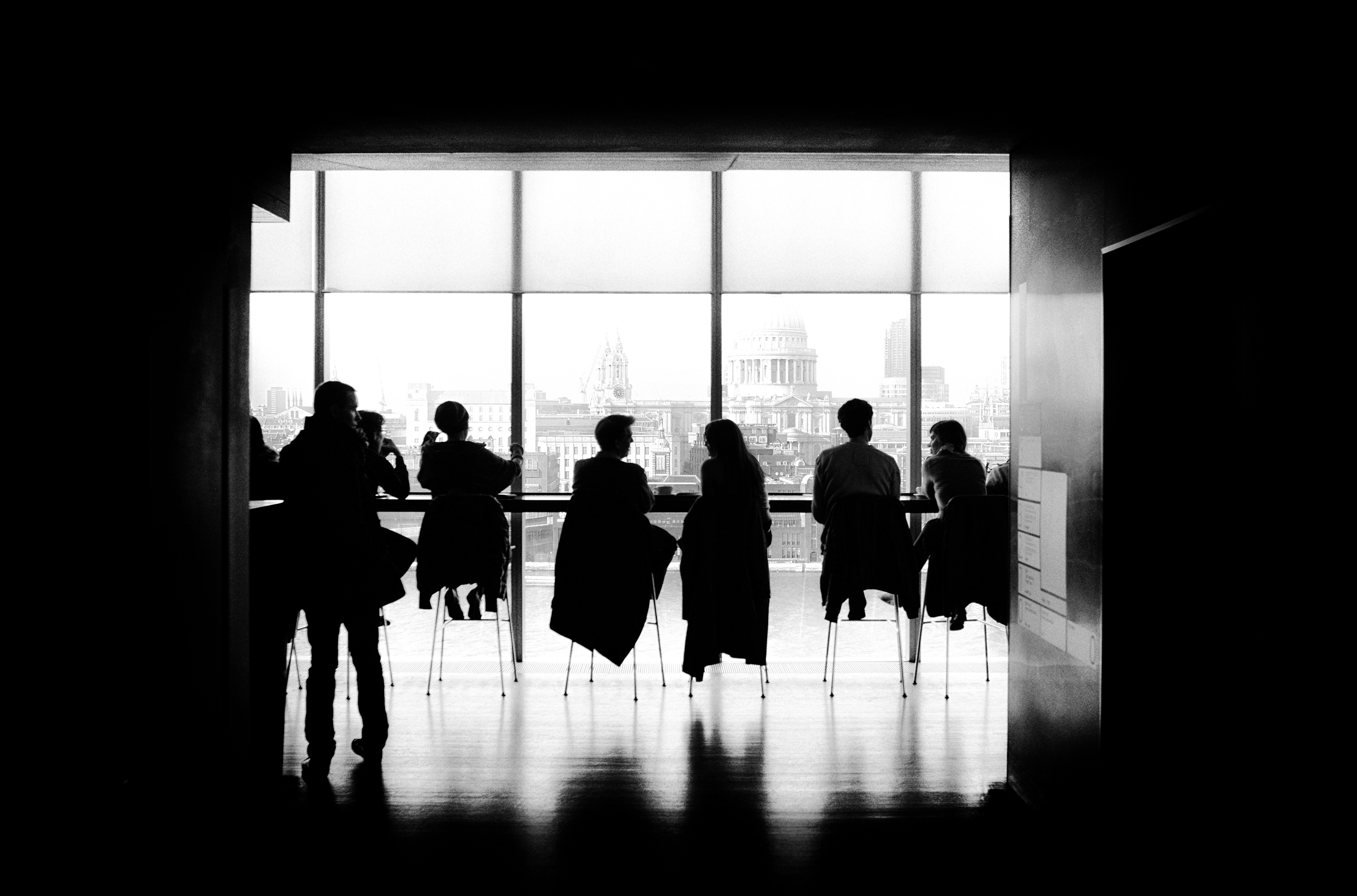 Black and white photo with people seated in a meeting room, set against a full window pannel looking out onto the city