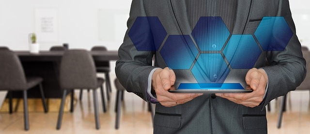 Man holding a tablet is projecting illuminated interlocking honeycombe cells