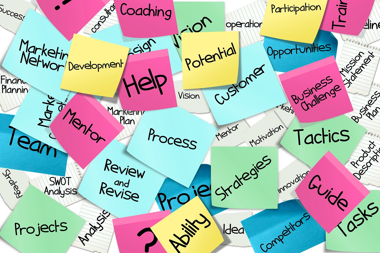 Different coloured sticky notes on a board saying process, help, strategies, tactics, guide etc