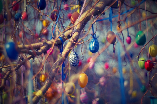 Hundreds of brightly patterned eggs hanging from the branches of a tree