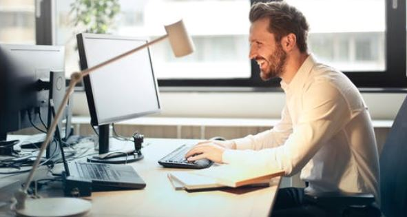 Image of a happy man sitting at a desk in front of a window with two flat screens and a keyboard