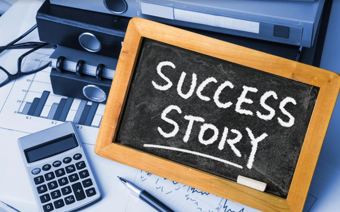 Files, charts and a calculator on a desk with a chalk board reading success story