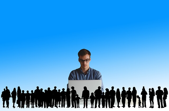 Group of 50 small shadow people, overseen by the image of a young person with a laptop
