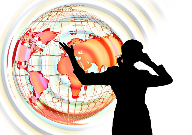 Picture of a world map in yellow and orange tones with the shadow figure of a woman pointing towards the map whilst talking on the phone
