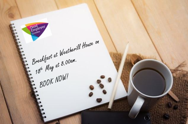 """Picture of a mug of black coffee on a table with a spiral bound, unlined note pad and pencil. The note pad has the Good Employer Croydon logo in the left-hand corner and free style writing saying """"Breakfast at Weatherill House on 18th May at 8.00am, book now!"""""""