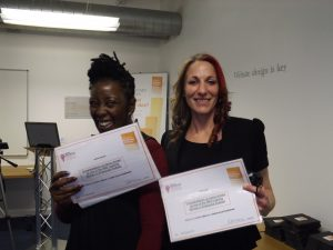 Two training course attendees holding their certificates