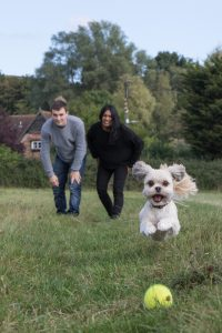 Jack and Aneisha with their dog Smudge playing ball in a Croydon field