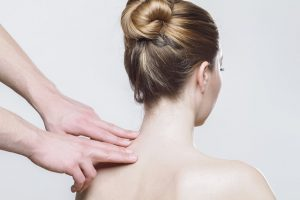 Photo of a woman facing away from the camera, having physiotherapy on her neck